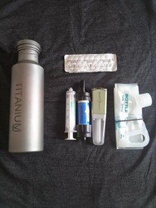 Inside the pouch, left to right: filter cleaning syringe, Sawyer Mini, and Steripen Freedom