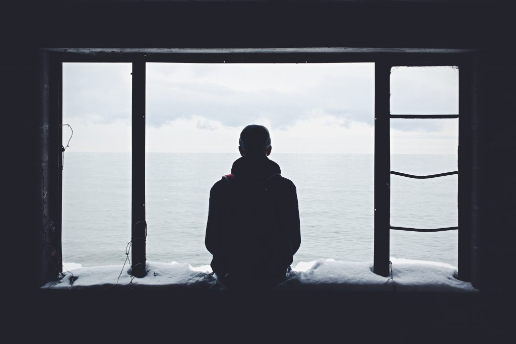 Man sitting alone on window ledge