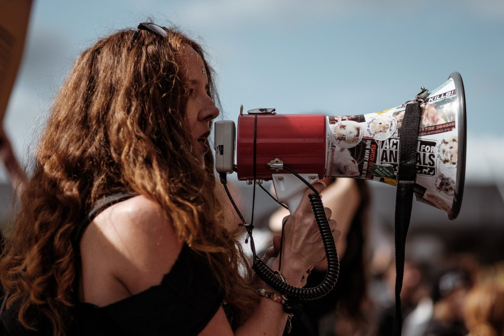 Woman shouting into megaphone at a protest